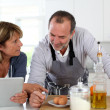 Senior couple having fun in home kitchen — Stock Photo
