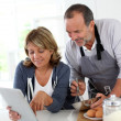 Senior couple having fun in home kitchen — Stock Photo #13939961