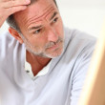 Senior man looking at his hair in mirror — Stock Photo #13939971