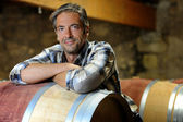 Smiling winemaker leaning on wine barrel in winery — Stock Photo