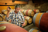 Winemaker getting sample of red wine from barrel — Stock Photo