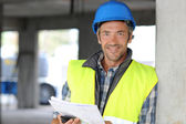 Smiling construction manager standing on building site — Stock Photo
