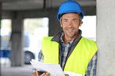 Sonriente gerente de construcción en obra — Foto de Stock