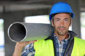 Construction worker on site holding pipe — Stock Photo