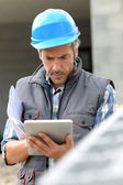 Entrepreneur on construction site using electronic tablet — Stock Photo