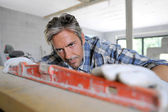 Man met niveau in huis in aanbouw — Stockfoto