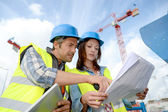 Construction manager and engineer working on building site — Stockfoto