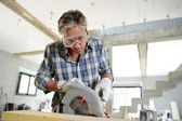 Man using electric saw inside house under construction — Stock Photo