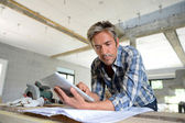 Entrepreneur in house under construction checking plan — Foto de Stock