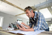 Entrepreneur in house under construction checking plan — Stockfoto