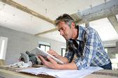 Entrepreneur in house under construction checking plan — Stock Photo