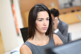 Woman working in office in front of desktop computer — Stock Photo