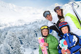 Family of four at the mountain in winter — Stockfoto