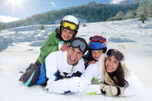 Happy family laying down in the snow — Foto Stock