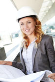 Portrait of beautiful woman architect looking at plan — Stock Photo