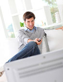 Man relaxing in sofa watching tv — Stock fotografie