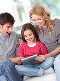 Happy family at home using electronic tablet — Stock Photo