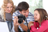 Family looking at pictures on camera screen — Stock Photo