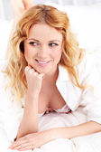 Beautiful smiling woman laying on bed — Stock Photo