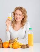 Attractive blond woman drinking orange juice — Stock Photo