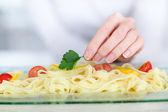 Closeup on woman putting parsley on pasta dish — Stock Photo
