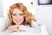 Piękne blond kobieta relaksujący na kanapie — Zdjęcie stockowe