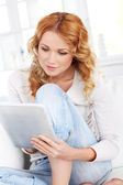 Beautiful blond woman using electronic tablet — Stock Photo