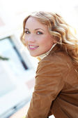 Beautiful blond woman in town by sunny day — Stock Photo