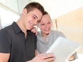 Friends in school corridor using electronic tablet — Stock Photo