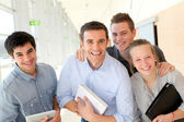Portrait of students with teacher in school building — Stock Photo