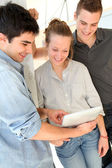 Group of friends at school using tablet — Stock Photo