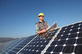 Man standing by solar panels with construction plan — Stock Photo