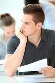 Portrait of student boy doing written exam — Stock Photo