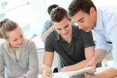 Teacher helping students with assignment — Stock Photo