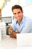 Smiling architect sitting in office — Stock Photo