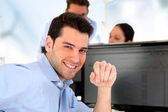 Smiling trader in front of desktop computer — Stock Photo