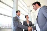 Business partners shaking hands in meeting hall — Stockfoto