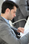 Young man filling in application form — Stock Photo