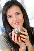 Portrait of young woman drinking herbal infusion — Stock Photo