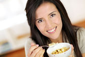 Beautiful brunette eating cereals in the morning — Stock Photo