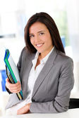 Cheerful saleswoman holding files — Stock Photo