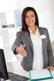Portrait of beautiful smiling hostess giving handshake — Stock Photo