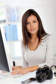 Young woman photo reporter sitting in front of desktop computer — Stock Photo