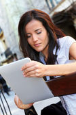Woman sitting on public bench with tablet — Stock Photo