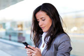 Businesswoman sending message with smartphone — Stok fotoğraf