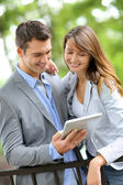 Couple standing in park with electronic tablet — Stock Photo