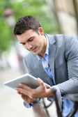 Man using electronic tablet outside in town — Stock Photo