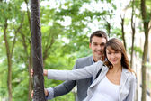 Portrait of cheerful couple standing by lamppost in town — Stock Photo