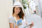 Woman in the street of Paris looking at tourist guide — Stock Photo