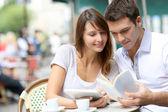 Pareja en una terraza de la cafetería leyendo libro turístico — Foto de Stock